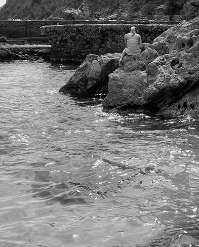 Quiet Times #41 by Jeremy Chin - Girl Sitting on the Rocks in Monterosso, Cinque Terre, Italy